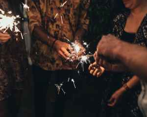 group of people with sparkling bengal lights