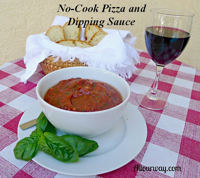 All Our Way no-cook pizza and dipping sauce in a white bowl on a table with a bread basket of sliced bread and a glass of red wine on the side. @allourway.com