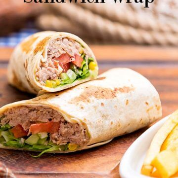 Tuna salad wrap with corn, lettuce, tomatoes, and avocados on a wooden board and a coiled rope in background.