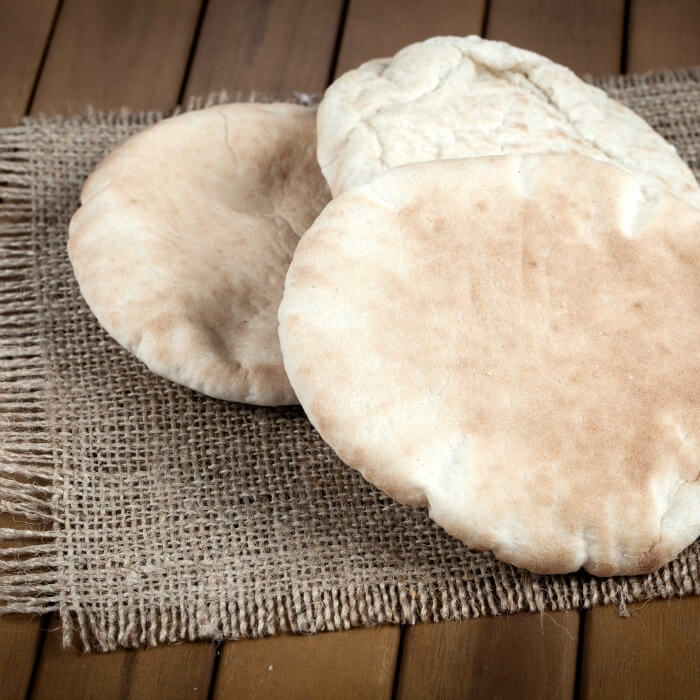 Two pitas lay on a burlap placemat. The pitas are round and lightly browned.