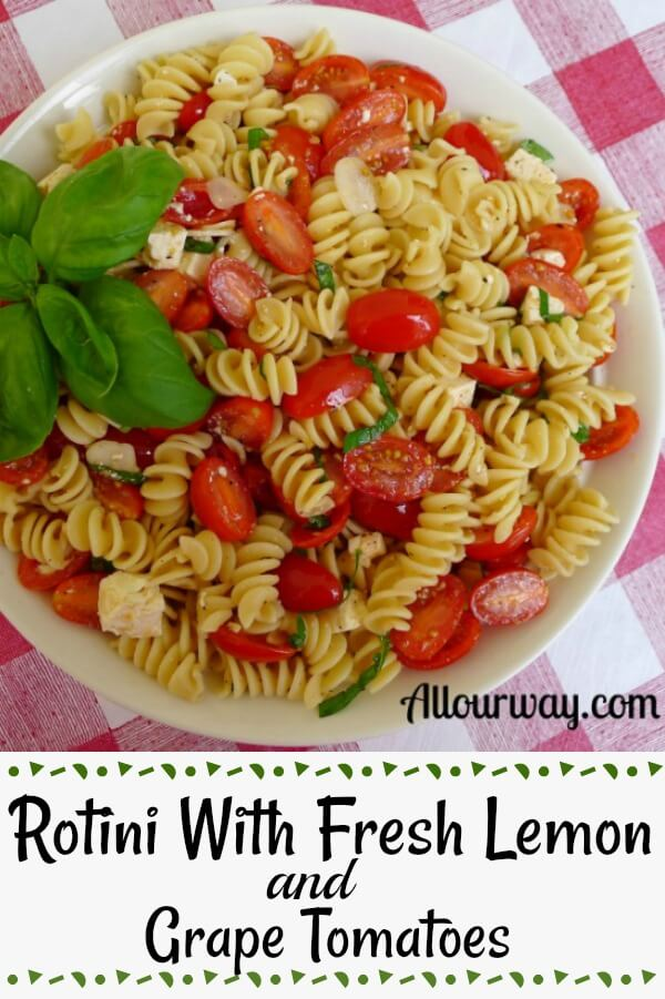 Rotini pasta with halved grape tomatoes, chunks of white ricotta salta in a white bowl on top of a red and white checkered tablecloth.