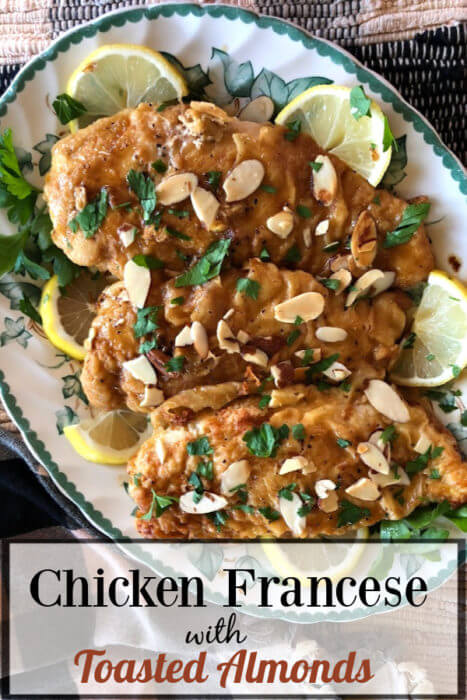 Three Chicken cutlets on a green edged platter. The chicken is topped with toasted almonds and parsley with lemon slices on plate.