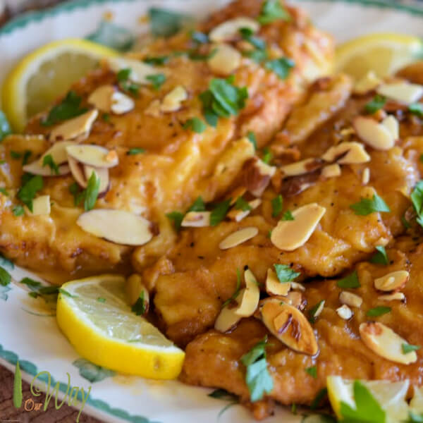 Golden brown chicken breasts on a green edged platter with lemon slices, toasted almonds, and chopped parsley.