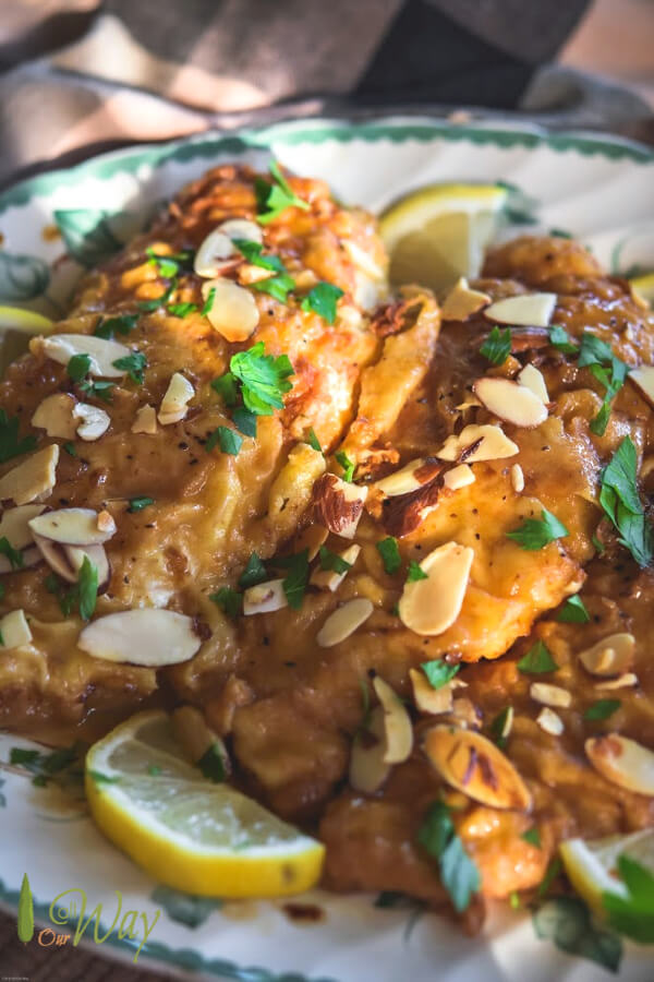 Golden brown chicken cutlets on green edged platter with lemon slices around plate and toasted almonds and parsley on top of chicken.