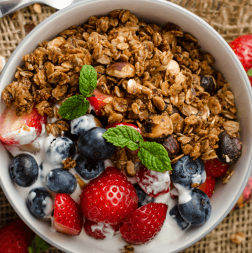 A bowl of homemade granola with blueberries and strawberries in the bowl with yogurt on the side of the granola.