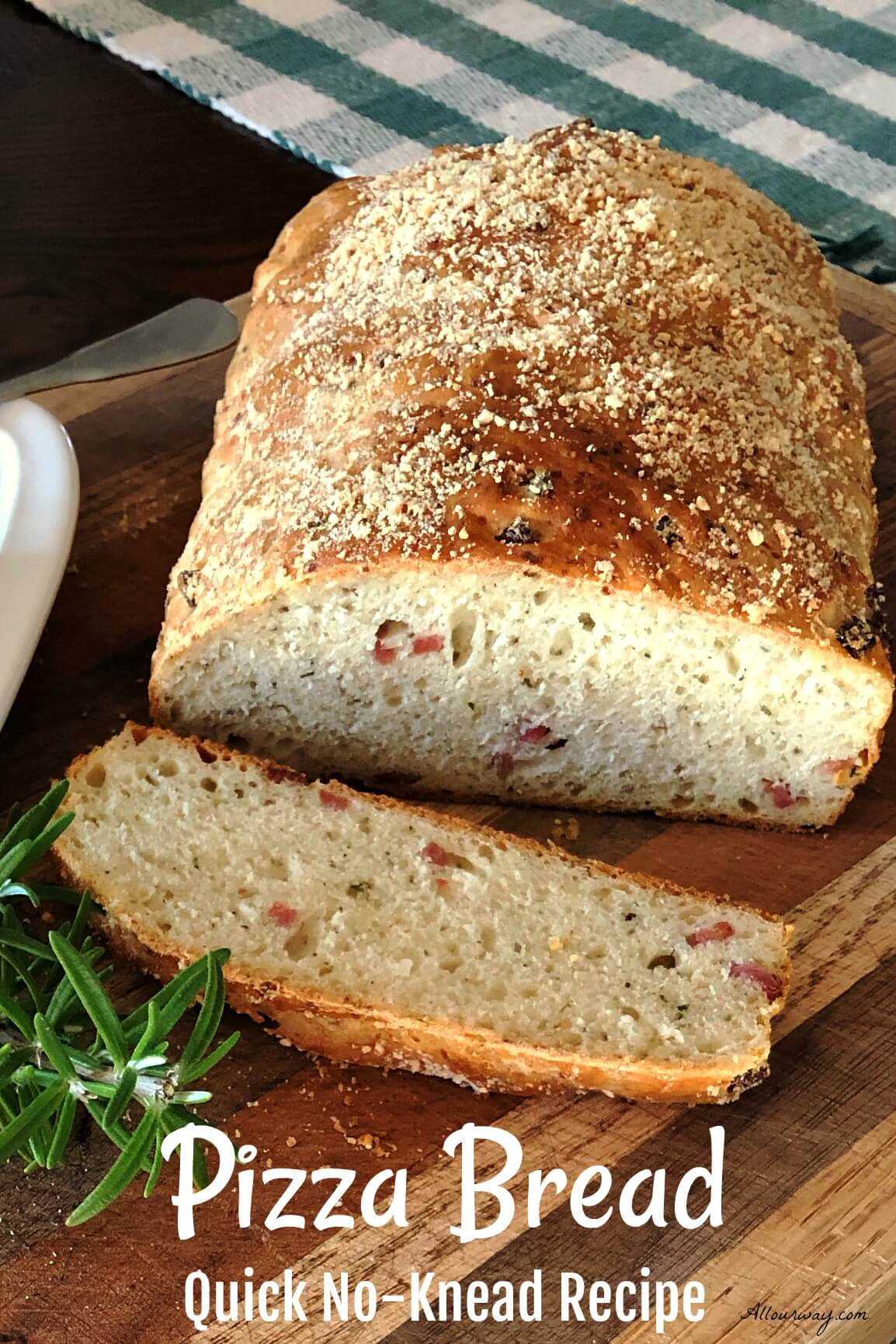Loaf of golden brown pizza bread sliced on a cutting board with specks of salami and herbs studding the loaf and slice.