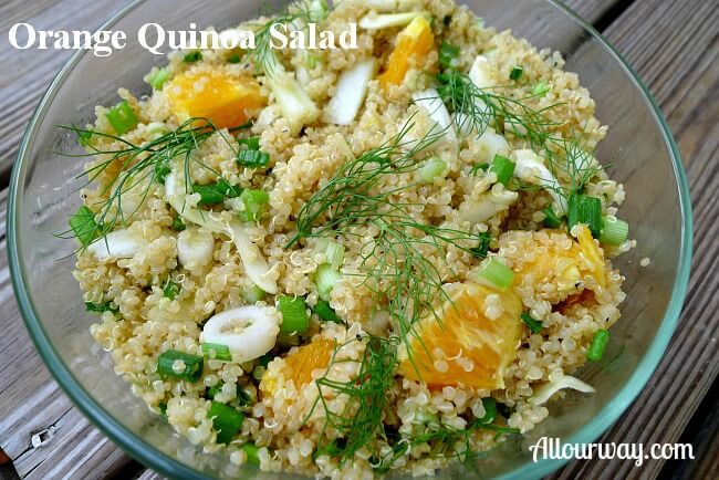 A large clear glass bowl filled with orange quinoa salad and fennel chunks. Green fennel fronds garnish the top of the salad.