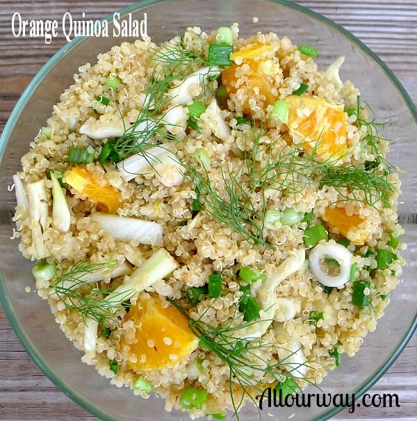 A clear glass bowl filled with Orange Quinoa Salad. Orange chunks and fennel pieces on top of quinoa. Fennel sprigs act as garnish.
