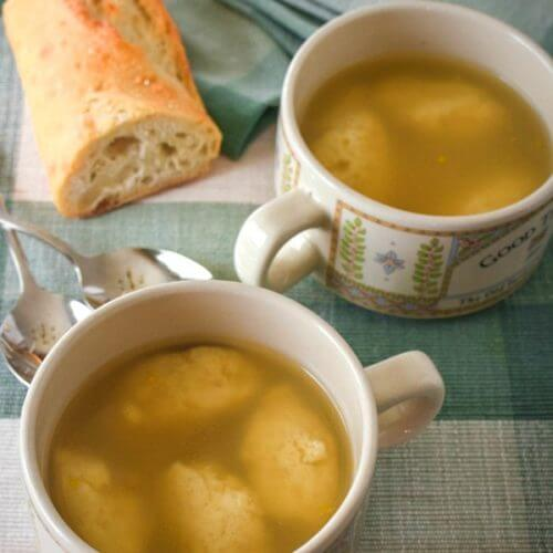 Two cups of chicken broth with cheese dumplings on a green plaid placemat with a partial loaf of Italian bread .