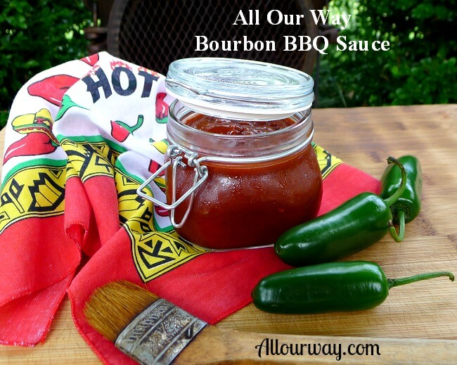 Spicy Bourbon Barbecue Sauce in a canning jar with a red pepper print bandana, green jalapeño peppers and a basting brush on a wood cutting board.