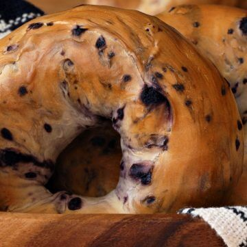 Close up of a fruit nut brown bagel in a white linen lined wooden basket.