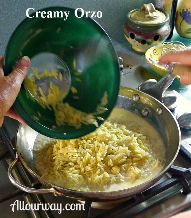 Cooked orzo in a green glass bowl poured into the sauce in the stainless steel saucepan.