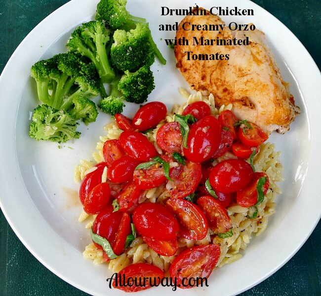 A white plate with a drunken chicken breast, creamy orzo with red marinated grape tomato halves and several small green broccoli florets.