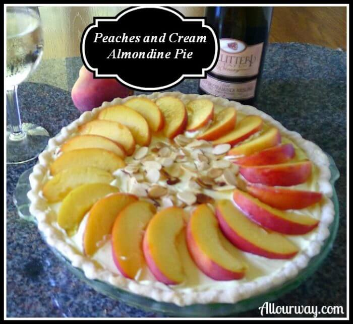 Peaches and Cream Almondine Pie with fresh sliced peaches on the top of the creamy pie with sliced almonds in the center. To the back is a glass of white wine and the wine bottle on the side. A fresh peach is behind the pie.