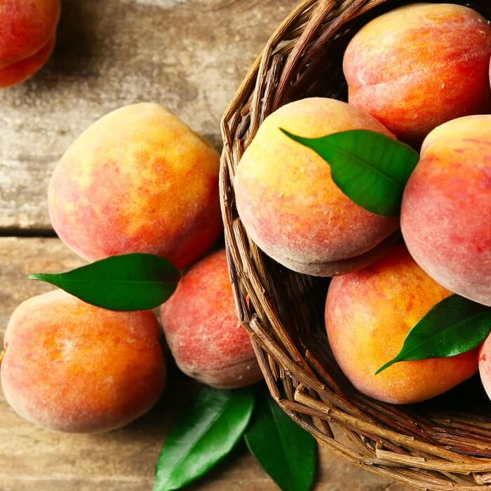 Ripe peaches with stems and green leaves in a wicker basked with several peaches spilling over onto a wooden table.