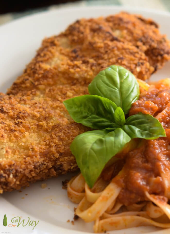 Chicken Milanese with tomato sauce covered fettuccini with a sprig of basil on white plate.