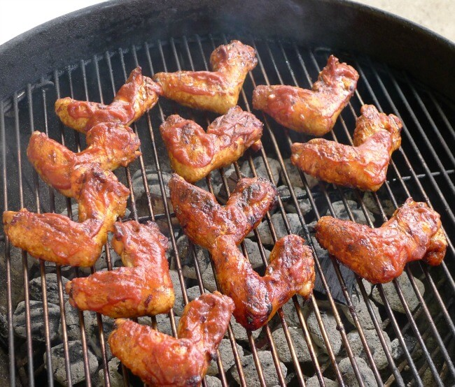 Chicken wings on the grill with All Our Way Bourbon Barbecue Sauce slathered over the top side.