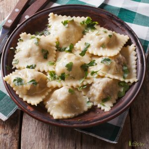 Homemade Italian ravioli with meat and cheese filling sprinkled with green parsley in a brown rustic bowl with wood handled fork and knife on a green and white plaid napkin on top of rustic wood table.