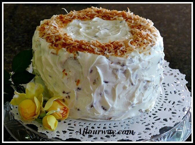 Three layer Italian Cream Cake with Toasted Coconut on a doily lined cake platter with three yellow rosebuds on the side. allourway.com