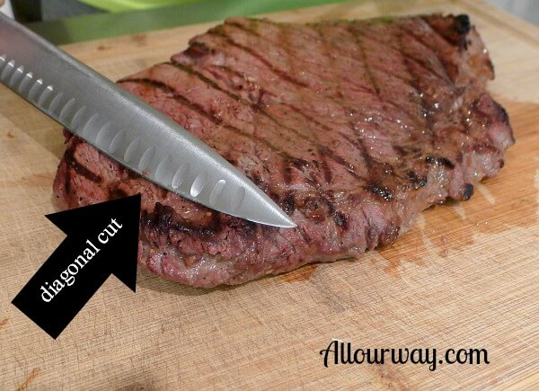 Grilled top round steak on a wooden cutting board with a knife cutting meat on diagonal.