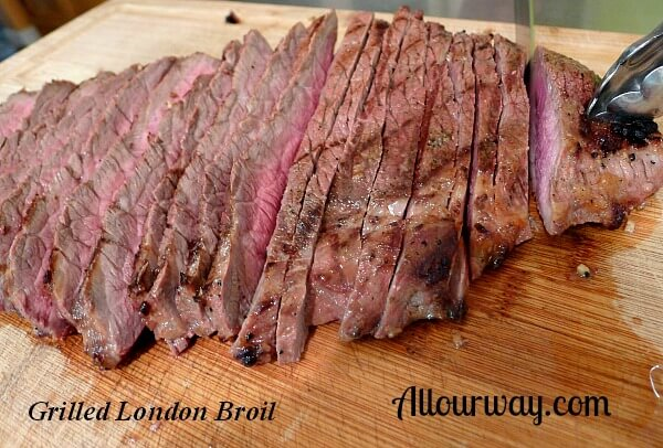 London Broil Marinated with Dijon mustard than grilled and sliced cross grain on wood cutting board.