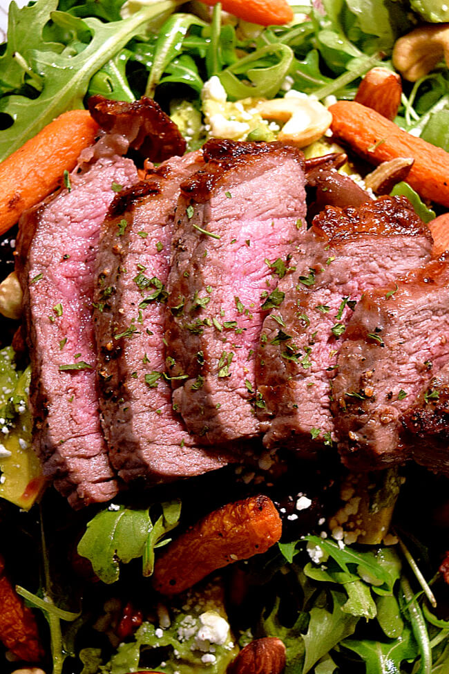 Sliced London broil on top of an arugula salad with grilled carrots.