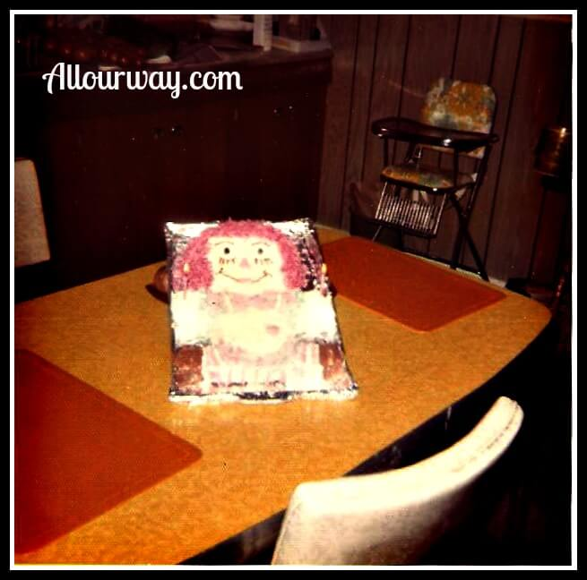 Raggedy Ann Cake for a Birthday on a yellow formica table.