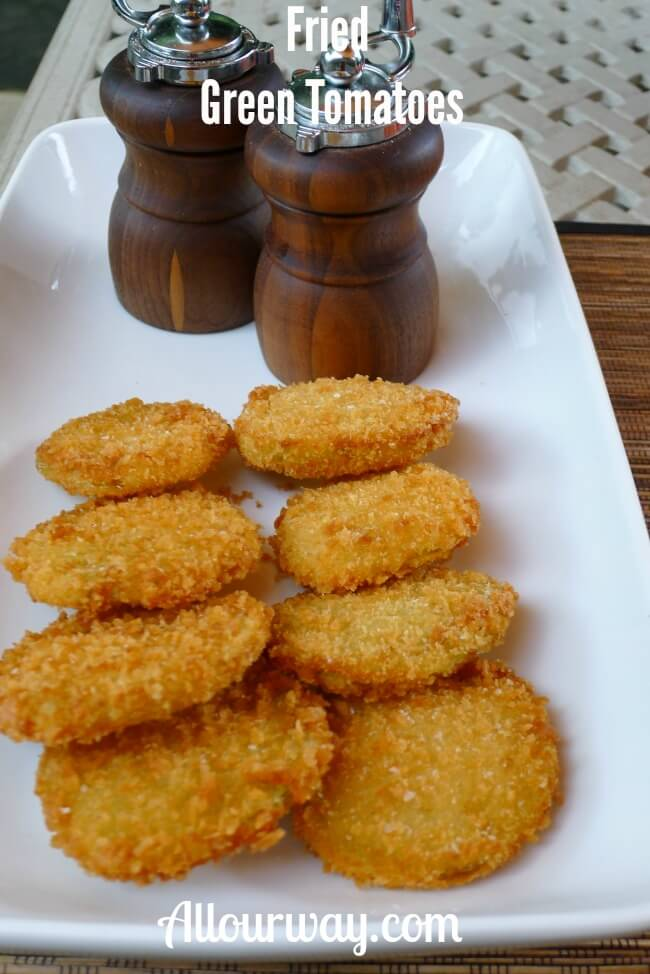 Fried Green Tomatoes Breaded with Panko Crumbs on a white platter with a wooden salt and pepper grinder at the top of the platter.