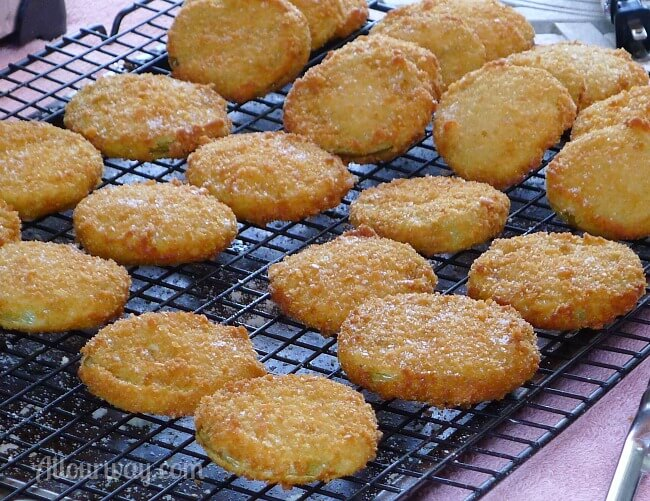 Crunchy Fried Green Tomatoes breaded with Panko Crumbs four rows lined up on a black wire cooling rack. a