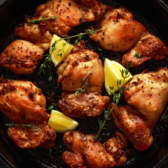 Browned Lemon Garlic Chicken Thighs in Cast iron skillet with rosemary and lemon