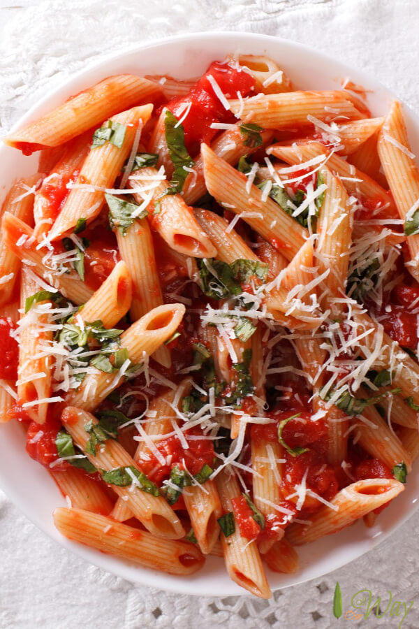 Closeup of penne pasta covered with a red sauce and sprinkled with green herbs in a white bowl.