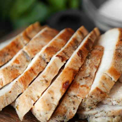 Perfect roast turkey breast sliced on a cutting board with a sprig go thyme in front.