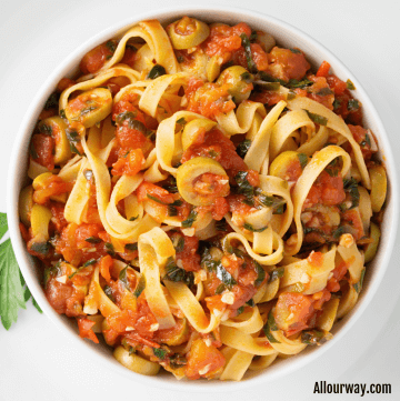 White plate filled with Fettuccini that is covered in a spicy Puttanesca Sauce.