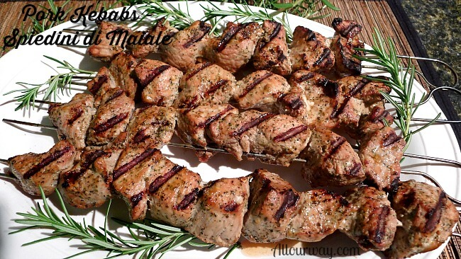 Four skewers of Pork Kebabs or Spiedini di Maiale on a white platter with rosemary sprigs surrounding them.