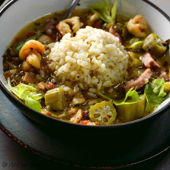 Closeup of Louisiana Shrimp Gumbo in brown bowl with a scoop of rice.
