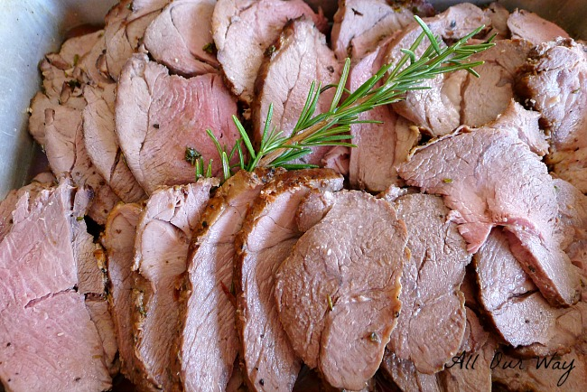 Roasted herbed leg of lamb with lamb slices in rectangular pan and spring of fresh rosemary on top.