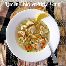 Lemon Chicken Orzo Soup in Bowl with Artisan Bread next to it and on top of black and tan napkin with matching placemat @allourway.com
