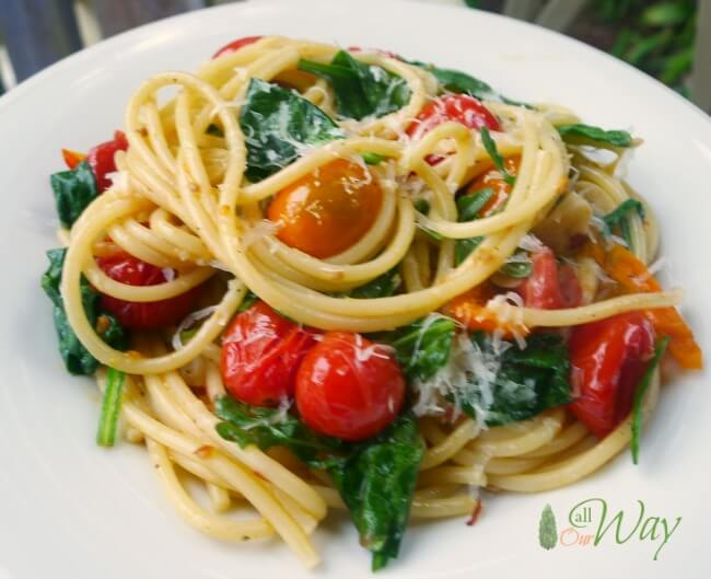 Roasted Grape Tomatoes and Garlic in Olive Oil with pasta on white plate.