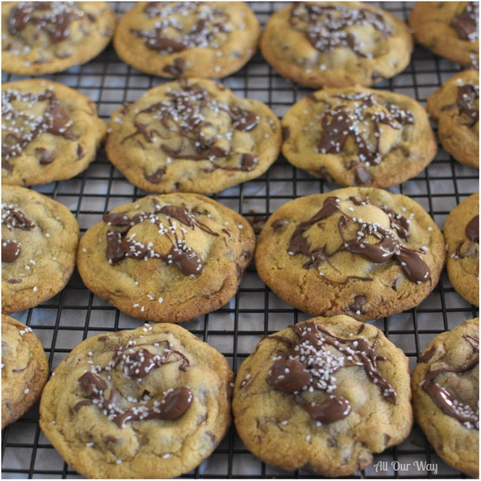 Salty Sweet Nutella Chocolate Chip Cookies are lined up in rows on a black cooling rack.