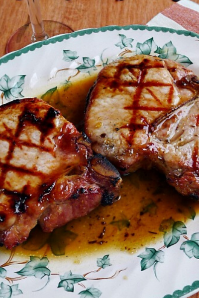 Two grilled pork chops on leaf patterned plate covered with maple glaze