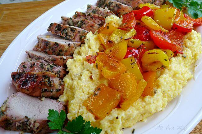 Grilled whole pork tenderloin slices with colored peppers over polenta on a white platter @ allourway.com