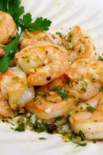 Grilled Shrimp with lemon , garlic and onions in white bowl with parsley