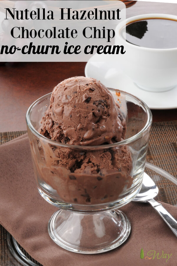 Two scoops of chocolate ice cream in glass goblet with white cup of coffee in background and silver spoon next to glass goblet.