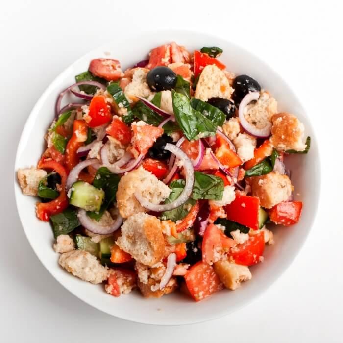 panzanella an Italian bread tomato salad in a white bowl with a white background.