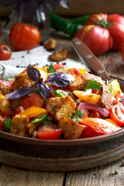 Panzanella an Italian bread salad in dark bowl with fork and tomatoes around it.