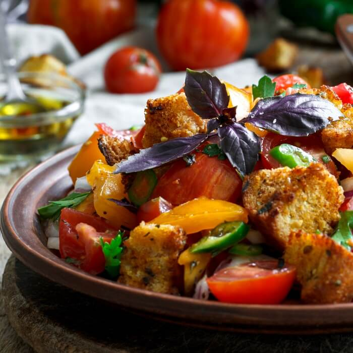 a close up of panzanella an Italian tomato bread salad in brown bowl with purple basil on top and tomatoes in background.