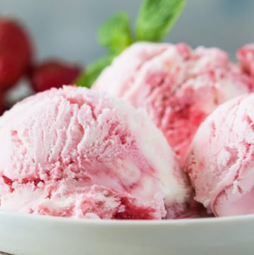 White bowl with 3 scoops of strawberry ice cream with mint leaves on top and ripe strawberries in background.