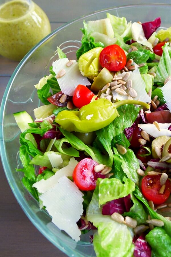 A glass bowl filled with red grape tomato halves, chopped romaine, radicchio, green olives, peperoncini, and sunflower seeds.