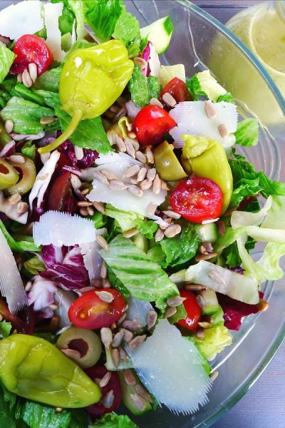 Tossed salad with romaine, radicchio, cherry tomatoes, and peperoncini in a glass bowl with green basil dressing on the side.