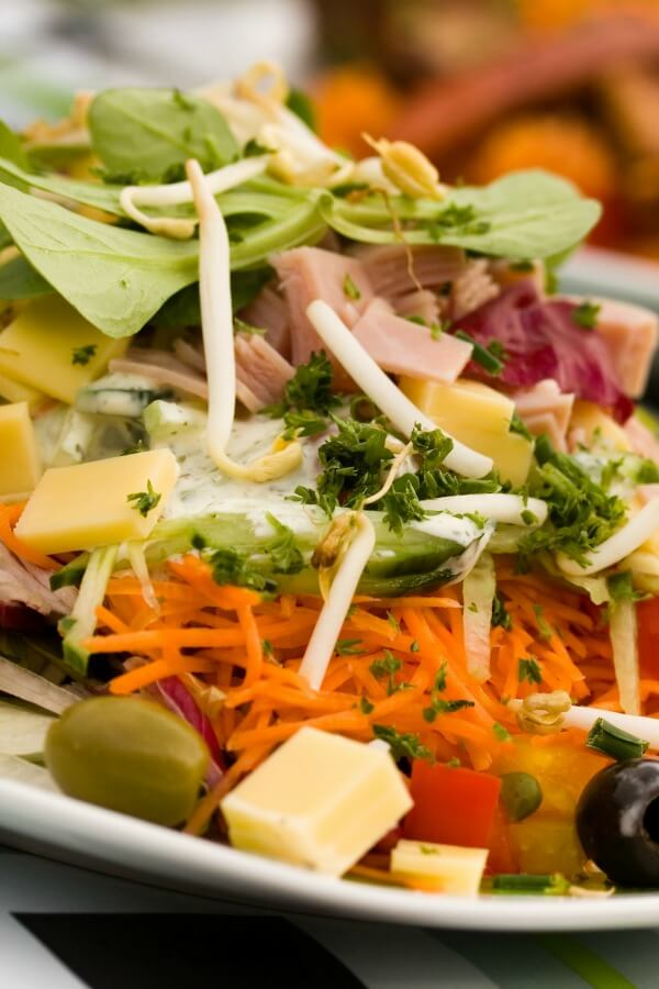 A chef salad closeup with salad greens, carrots, olives, cheese, and sliced meats, tomatoes.